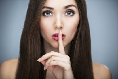 Woman with brown hair with fingers on lips